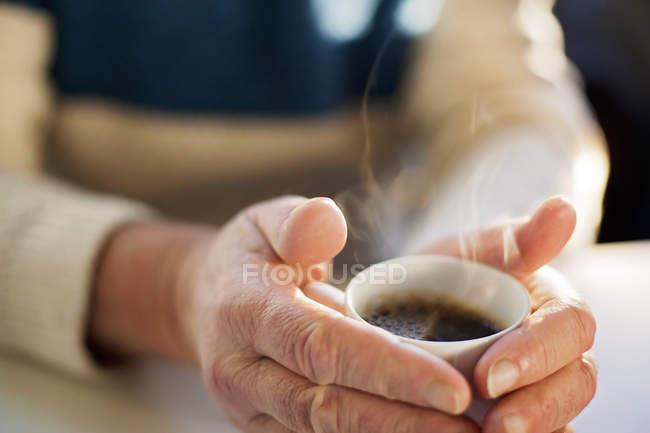 Mann hält Kaffeetasse am Tisch — Stockfoto