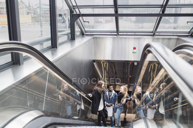 Friends moving up on escalator in glass building — Stock Photo