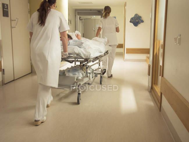 Enfermeras empujando a paciente en hospital - foto de stock