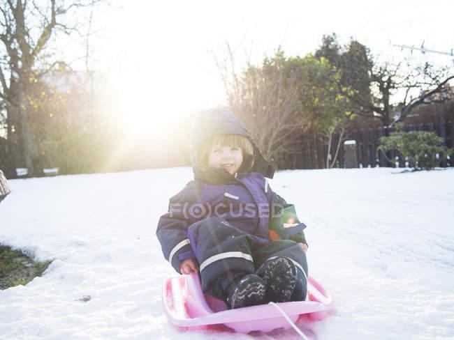 Garota feliz de trenó na neve — Fotografia de Stock
