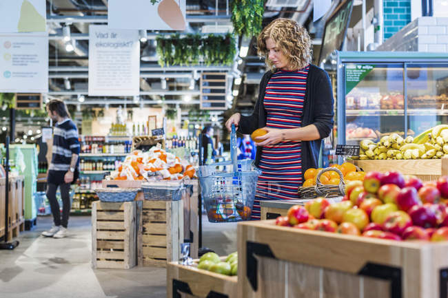 Woman buying oranges in supermarket — Stock Photo