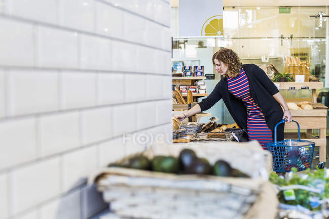 Woman buying bread in supermarket — Stock Photo