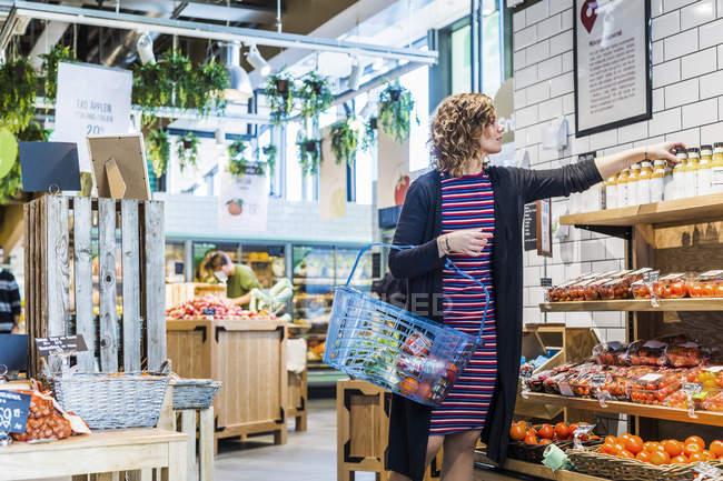 Woman buying fruit juice at supermarket — Stock Photo