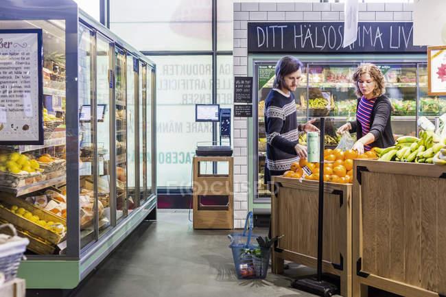Mulher e homem comprando laranjas no supermercado — Fotografia de Stock