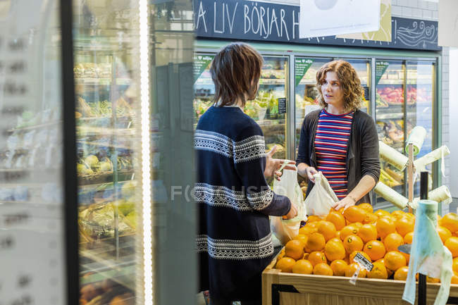 Woman and man talking while buying oranges — Stock Photo