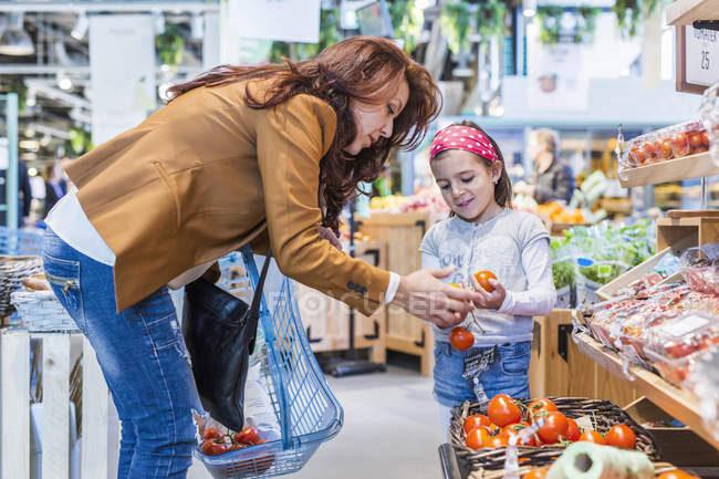 Mother and daughter buying tomatoes — Stock Photo