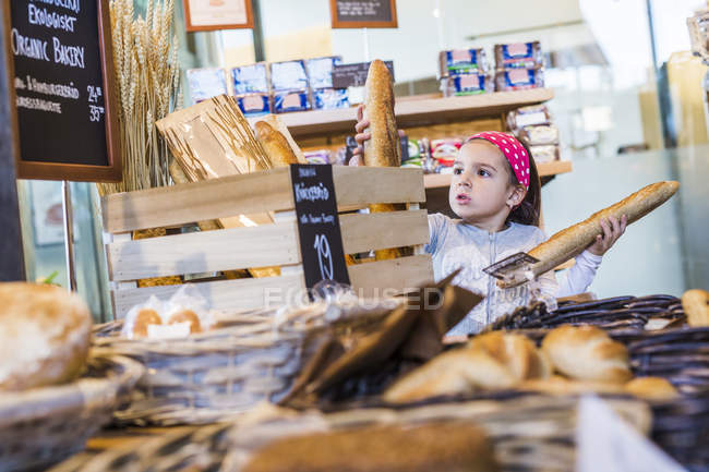 Cute girl buying breads — Stock Photo