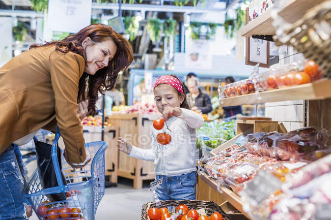 Girl holding tomatoes while standing by mother — Stock Photo