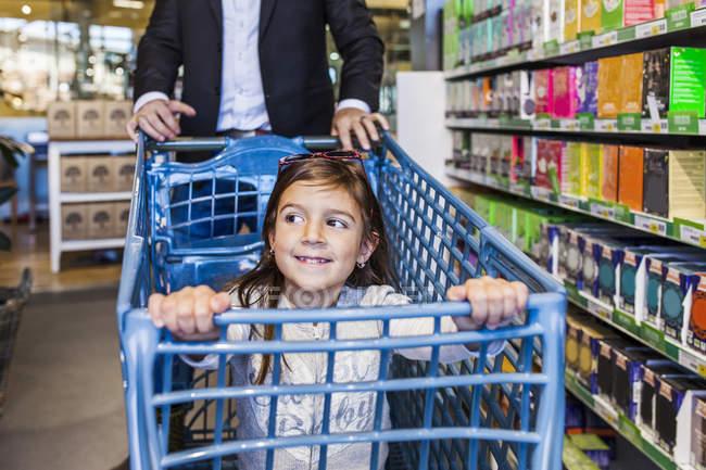 Smiling girl sitting in cart — Stock Photo