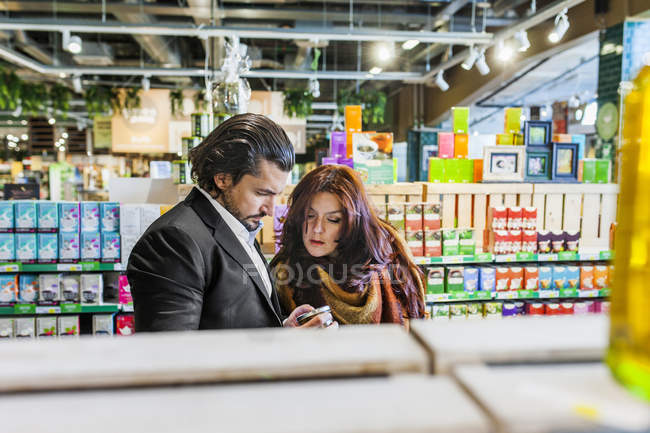 Couple shopping while standing in supermarket — Stock Photo