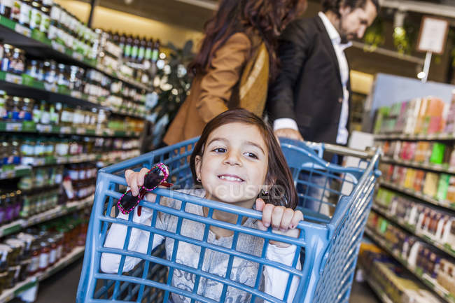 Happy girl sitting in cart — Stock Photo