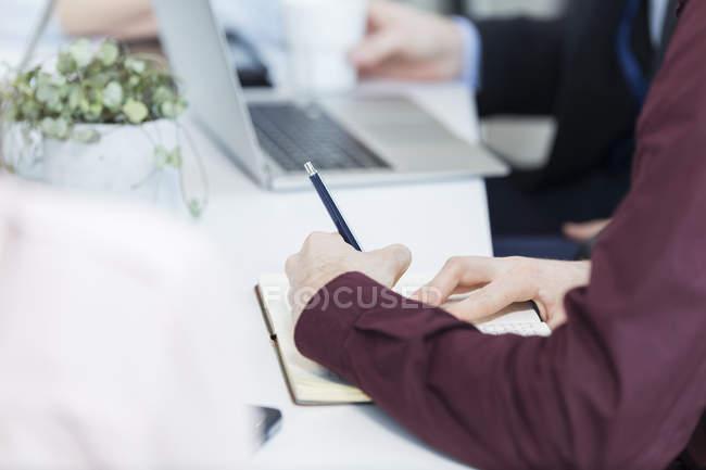 Бизнесмен пишет в книге на совещании — стоковое фото