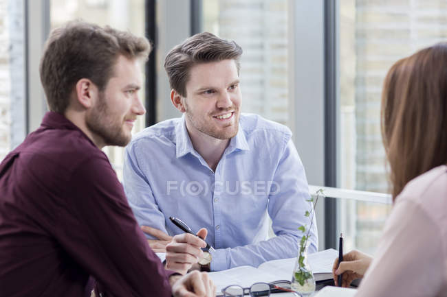 Businessmen looking at female colleague — Stock Photo
