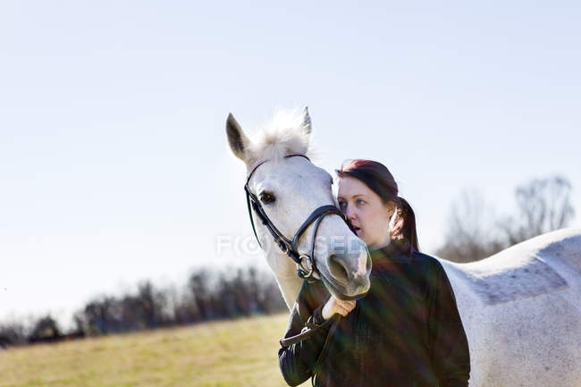Woman hugging horse on field — Stock Photo