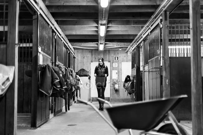 Женщина несет ведро во время прогулки в конюшне — стоковое фото