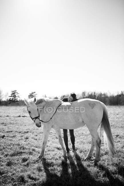 Woman leaning on horse — Stock Photo