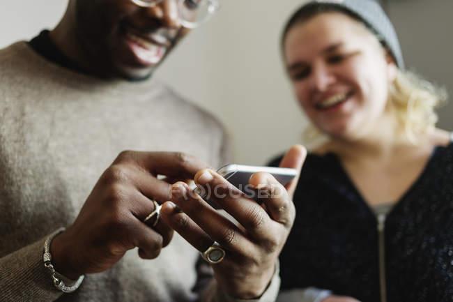 Happy friends using smart phone — Stock Photo
