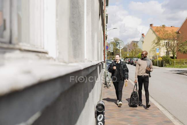 Freunde halten Kaffeetassen während des Gehens auf Bürgersteig — Stockfoto