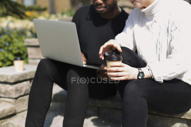 Homme utilisant un ordinateur portable sur les marches — Photo de stock