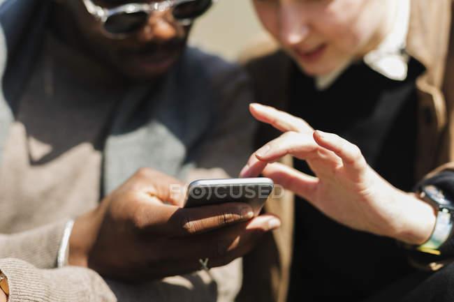 Freunde, die smartphone verwenden — Stockfoto
