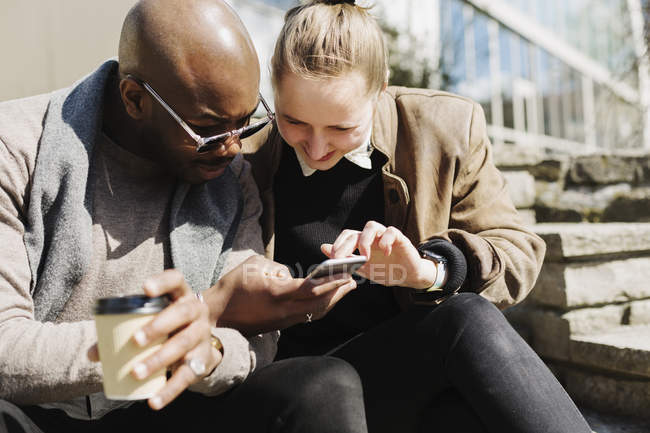 Friends using smartphone — Stock Photo