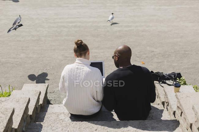 Деловые люди, использующие ноутбук на ступеньках — стоковое фото