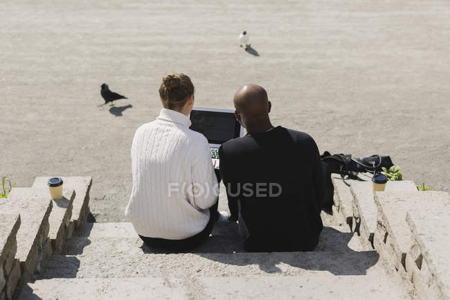 Businessman with female colleague using laptop — Stock Photo