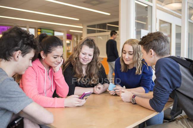 Crianças em idade escolar, através de telefones celulares na mesa — Fotografia de Stock