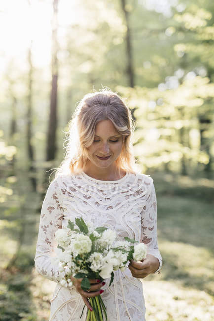 Bride Holding Bouquet im Wald — Stockfoto
