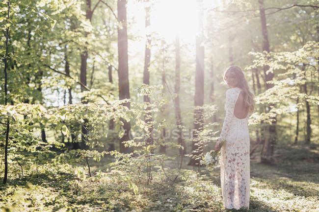 Noiva segurando buquê na floresta — Fotografia de Stock