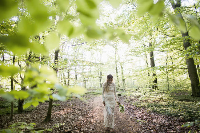 Bride holding bouquet in forest — Stock Photo
