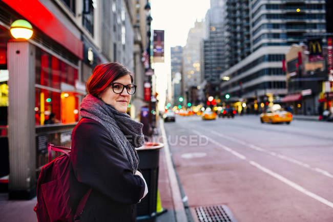 Donna in attesa sul marciapiede in città — Foto stock