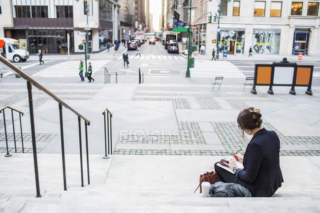 Donna d'affari che lavora mentre seduto su gradini — Foto stock