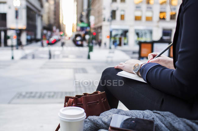 Mujer escribiendo por calle de la ciudad - foto de stock