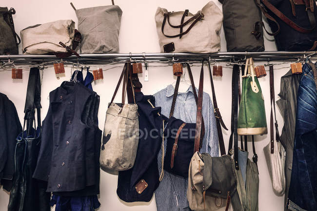 Clothing and bags hanging on hooks — Stock Photo
