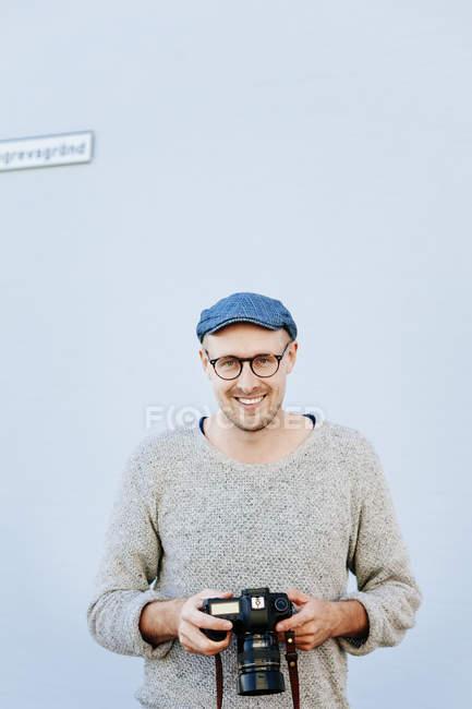 Confident man holding digital camera — Stock Photo
