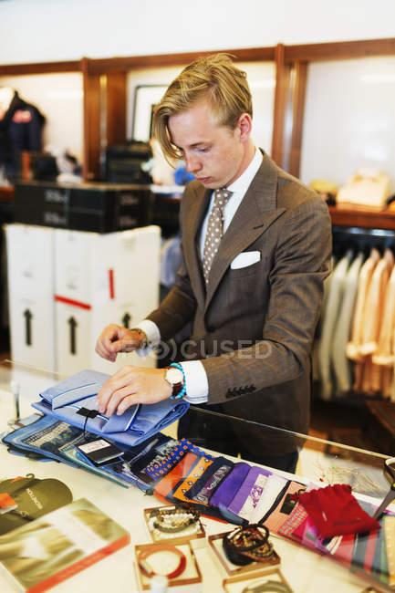 Sales clerk folding t-shirt — Stock Photo