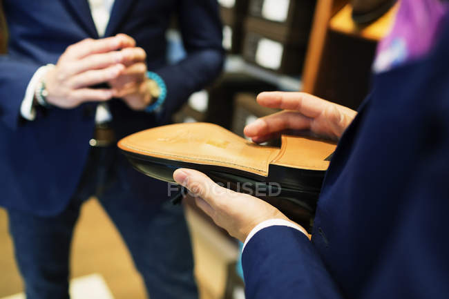 Salesman holding shoe — Stock Photo