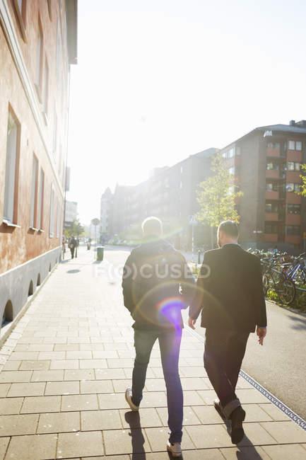 Men walking on sidewalk — стокове фото