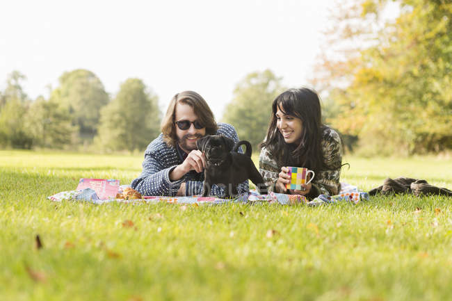 Happy young couple with puppy — Stock Photo