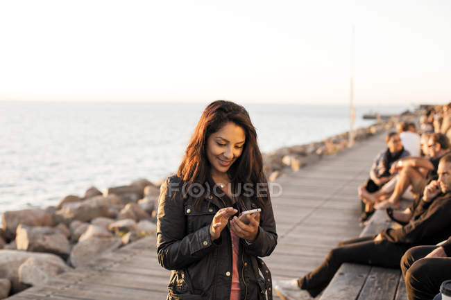 Smiling woman using mobile phone — Stock Photo