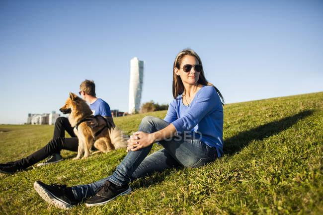 Casal com cachorro relaxante numa encosta gramada — Fotografia de Stock