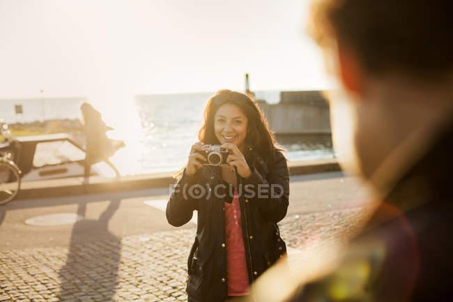 Giovane donna che fotografa amico — Foto stock