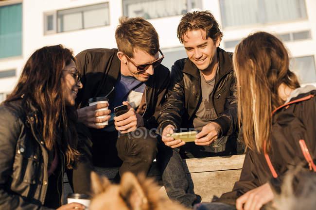 Amigos felizes usando telefone celular — Fotografia de Stock