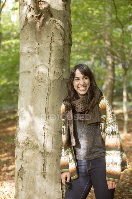 Woman leaning on tree in forest — Stock Photo