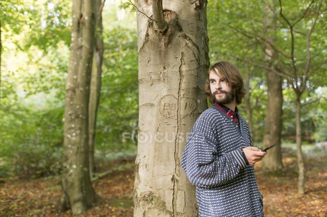 Uomo appoggiato sull'albero nella foresta — Foto stock