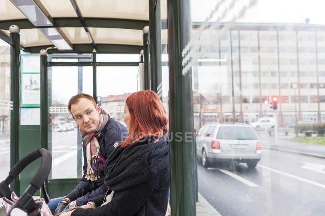 Пара на автобусной остановке — стоковое фото