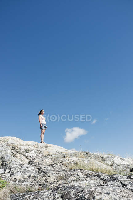 Woman standing on rocky hill — Stock Photo