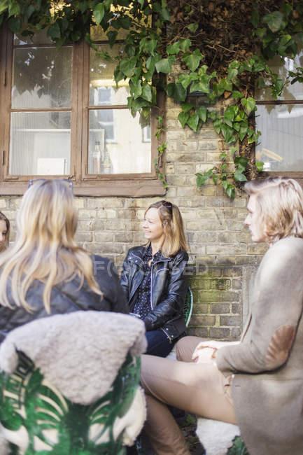 Donna felice che si siede con gli amici — Foto stock