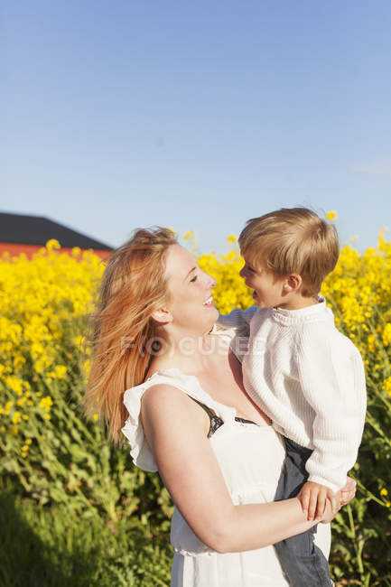 Happy woman carrying son — Stock Photo